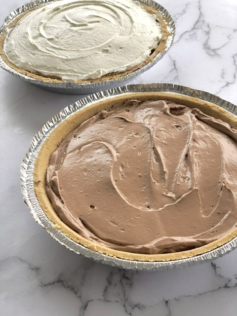 two no bake chocolate cream pudding pies in a graham crust one with fresh whipped cream on top