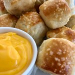 soft pretzels bites with coarse salt sprinkled on top and a small dish of cheddar cheese dipping sauce