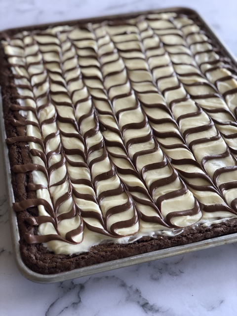 Close up shot of a sheet pan full of brownies with cream cheese frosting and a chocolate drizzle on top