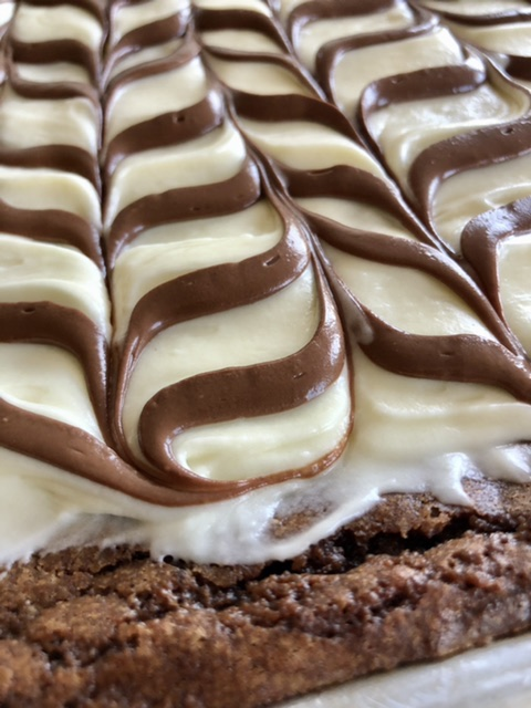 Close up fidgy chocolate brownie edge baked in a half sheet pan with cream cheese frosting and chocolate drizzle on top