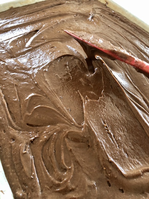 brownie batter being spread into a half sheet pan for baking