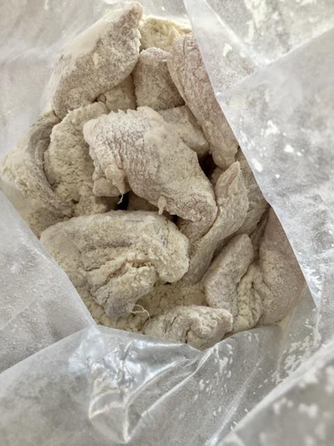 chicken strips coated in flour in a zip top bag