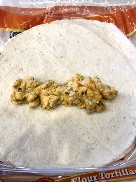 buffalo chicken ranch filling on a flour tortilla to roll up to make a taquito