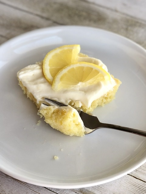 a fork cutting into a piece of lemon sheet cake