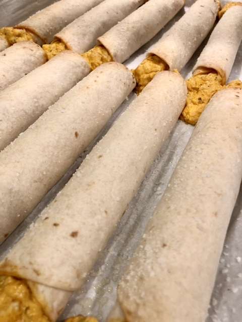 closeup shot of baked buffalo chicken taquitos with the filling melting out of the ends