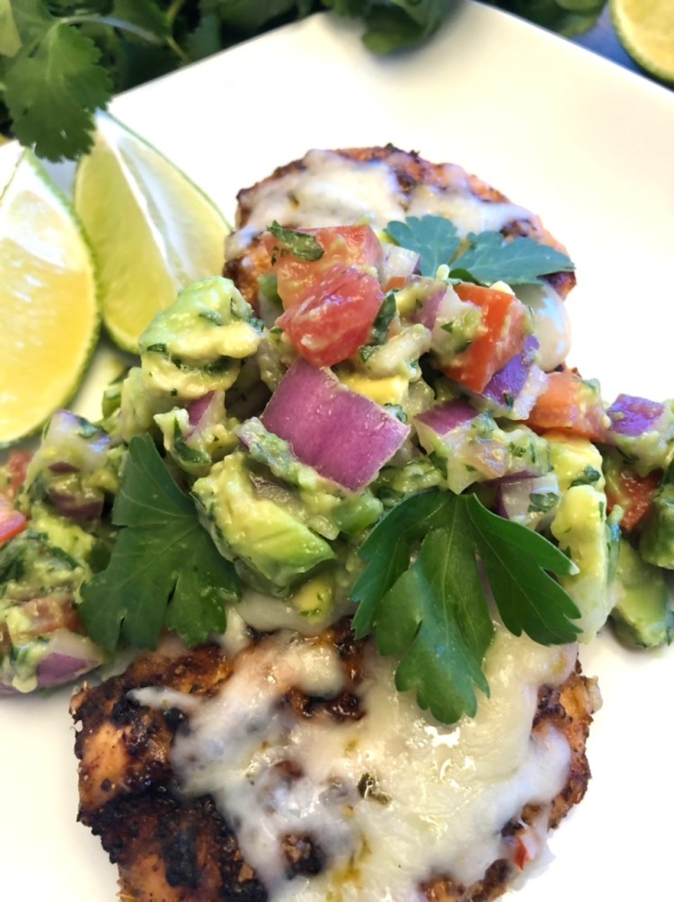 Grilled Chicken with Avocado Salsa on a plate with sliced limes