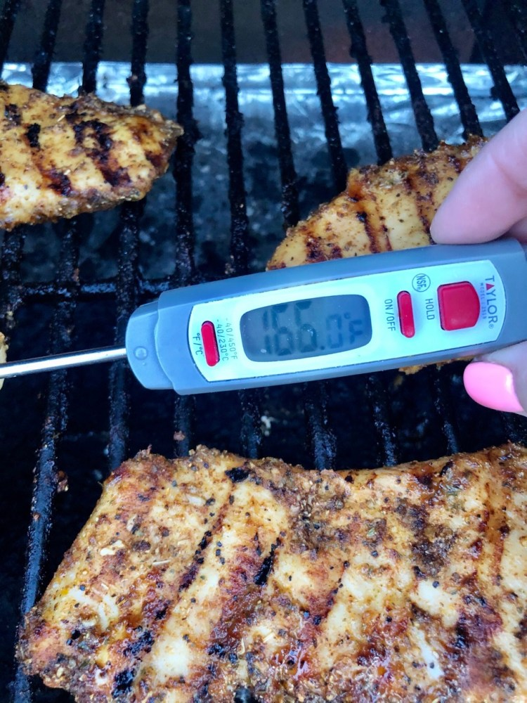 digital meat thermometer showing the internal temperature of the grilled chicken is 165 degrees