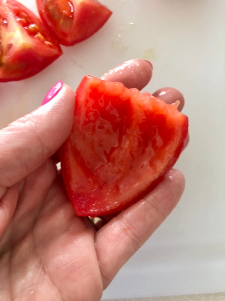 a piece of tomato with the seeds removed ready to chop/dice