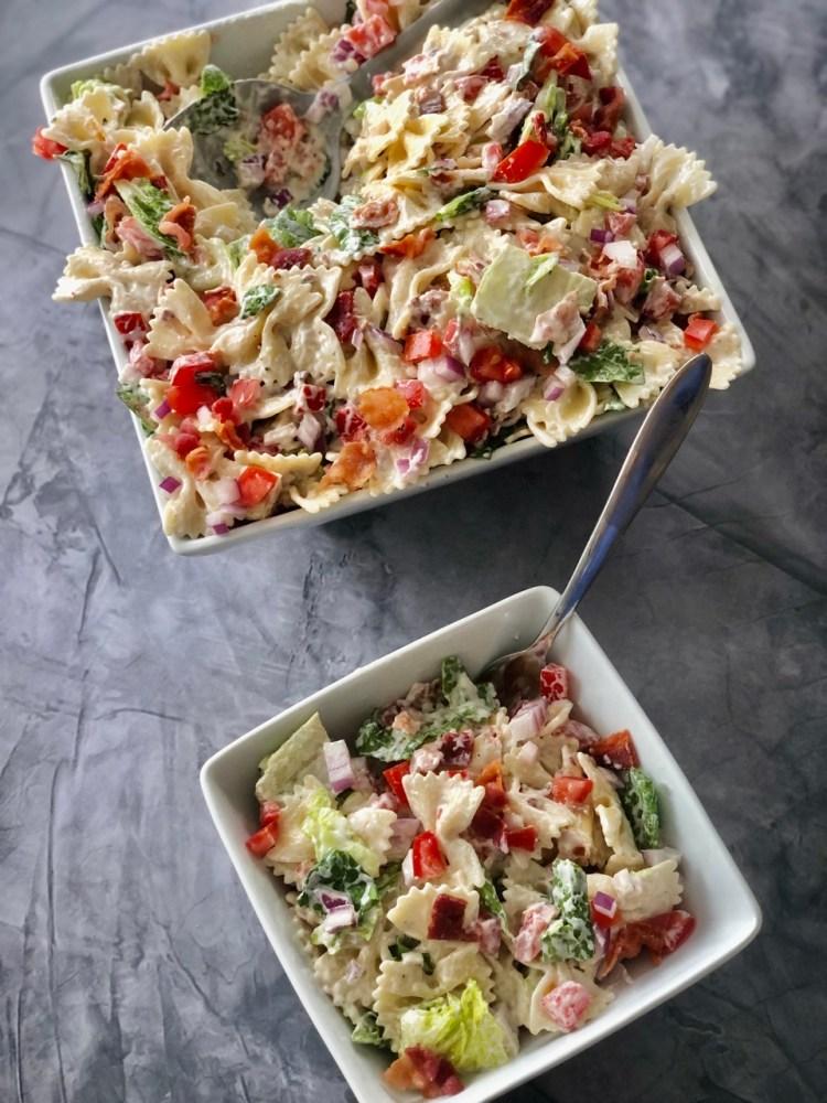 above shot of large serving bowl of blt pasta salad with a smaller dish of blt pasta salad beside it