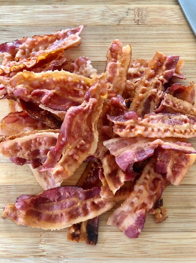 strip of thin cut bacon strips cooked on a wooden cutting board