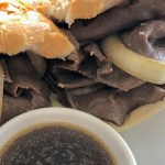 thin sliced roast beef and onions in a soft hoagie bun for an easy French dip sandwich with a side of au jus sauce for dipping
