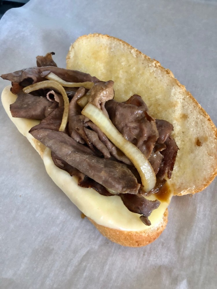 roast beef and onions added to a hoagie bun with melted cheese