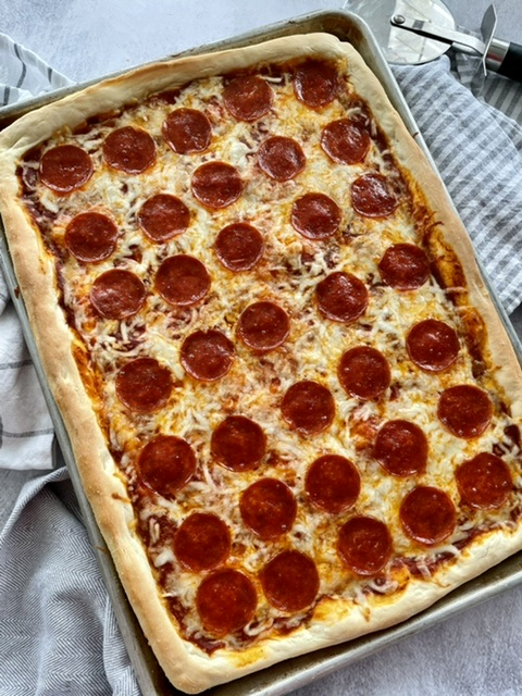 above shot of sheet pan pizza topped with pepperoni pizza