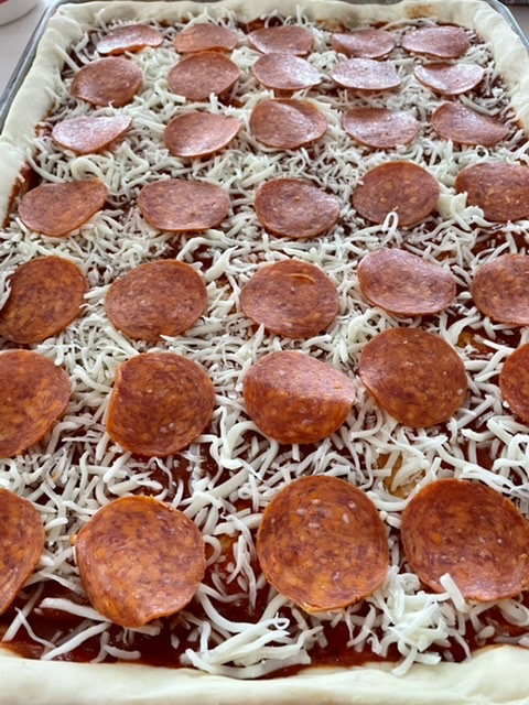 pepperoni added to sheet pan pizza