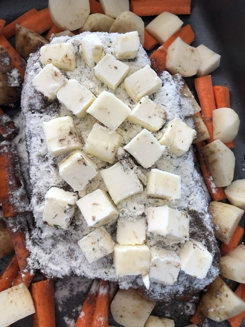 cubed butter added to the top of the seasonings on the pot roast