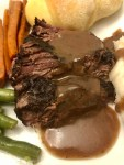 Pot roast with gravy and green beans and carrots on a plate