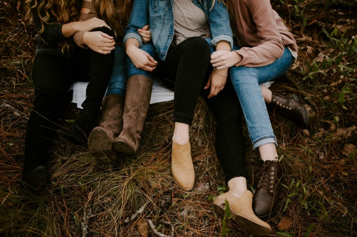 Anxiety Codependency Peer Support Three young women sitting arm in arm on the ground