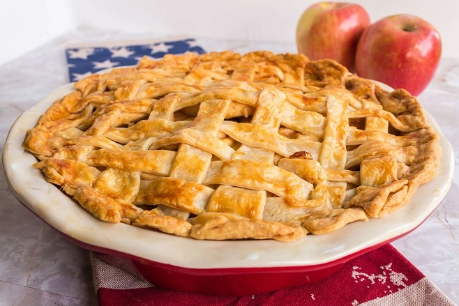 baked apple pie with weaved crust.  Two apples in back ground ontop of an american flag kitchen towel.