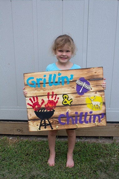 little girl holding homemade wooden gift for father