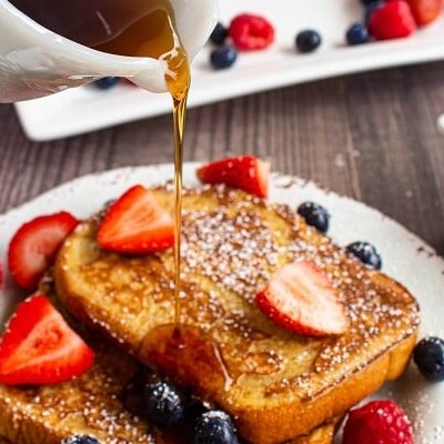 french toast with berries having syrup poured on top
