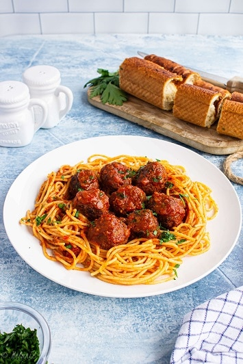 plate with spaghetti and meatballs with a loaf of bread in the background