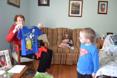 Grandma showing Aiden his new t-shirt, while Abby plays with Slinky on couch.