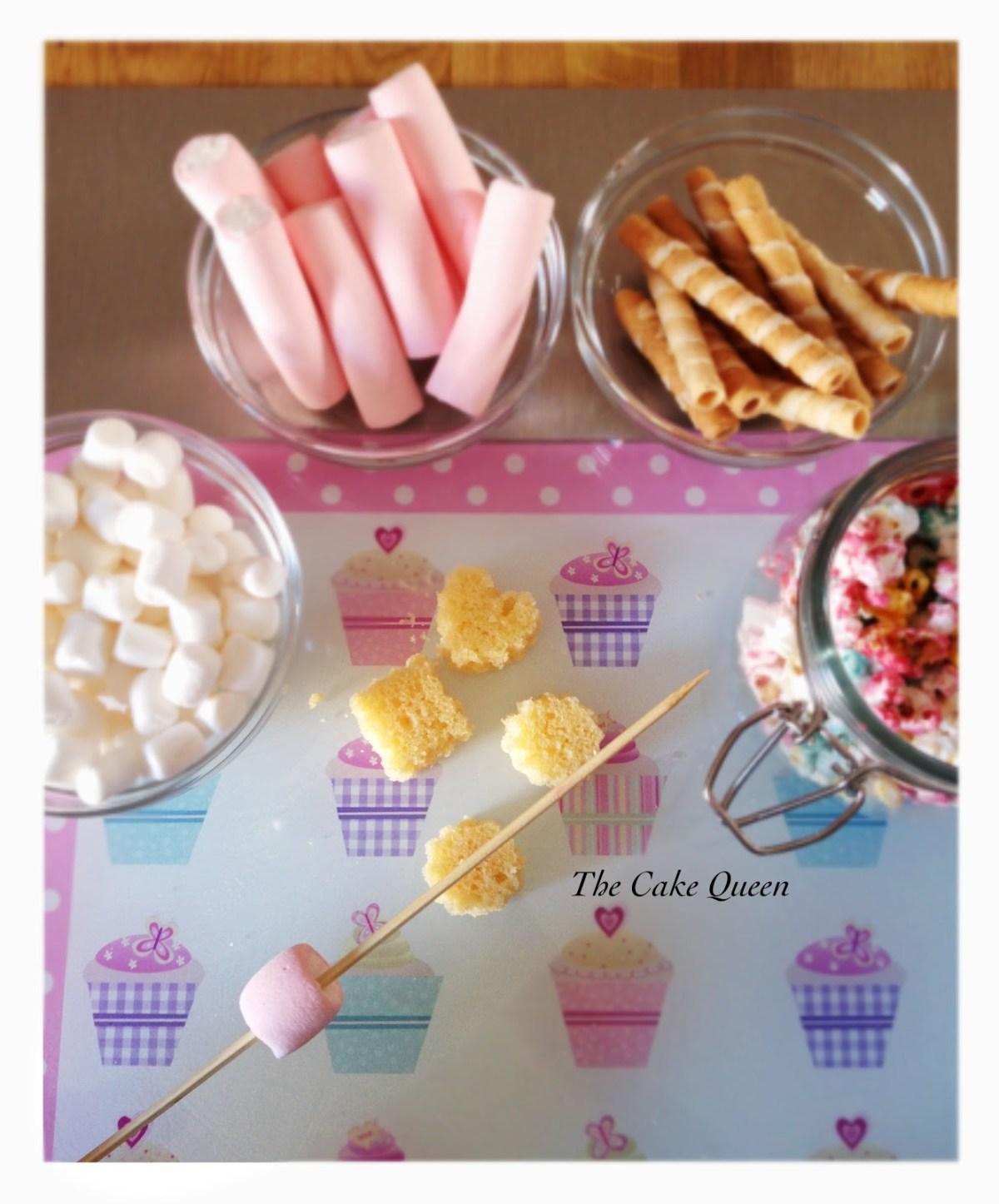 Brochetas de gominas: en nuestro palito de madera, empezamos a colocar nuestros marshmallows, trozos de tarta, fresas y nuestros barquillos, estos los colocamos en el orden que más nos guste