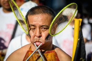 Faces pierced with badminton rackets at vegetarian festival