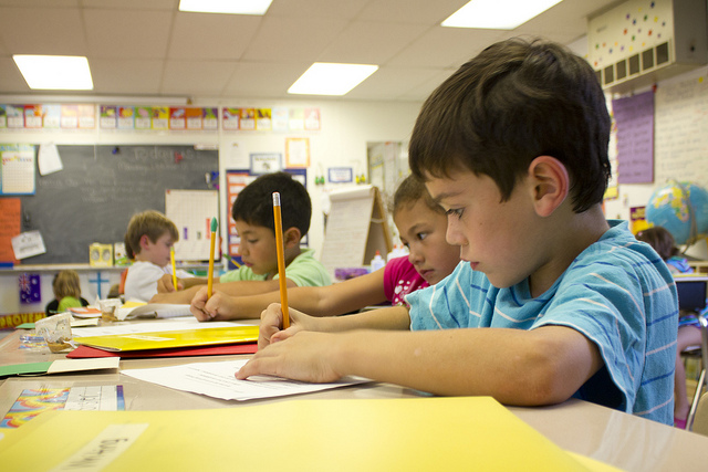 Elementary School students write with yellow pencils in classroom