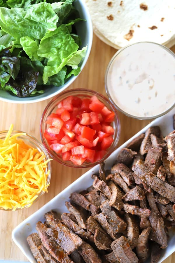 Carne asada chipotle flavored meat on a cutting board with cheese, tomatoes, lettuce and chipotle ranch.