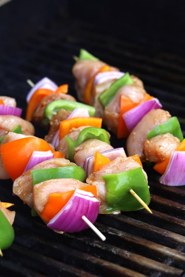 chicken kabobs on the grill with peppers and onions