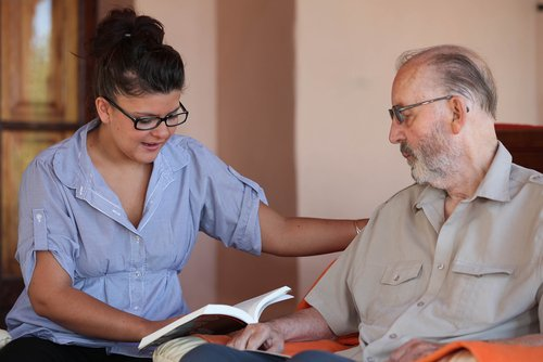 a home care aid reading to a client