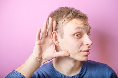 a man cups his hand around his ear to try to hear what someone's saying