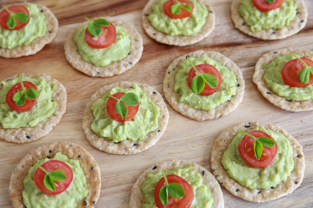 crackers with avocado, tomato, and basil