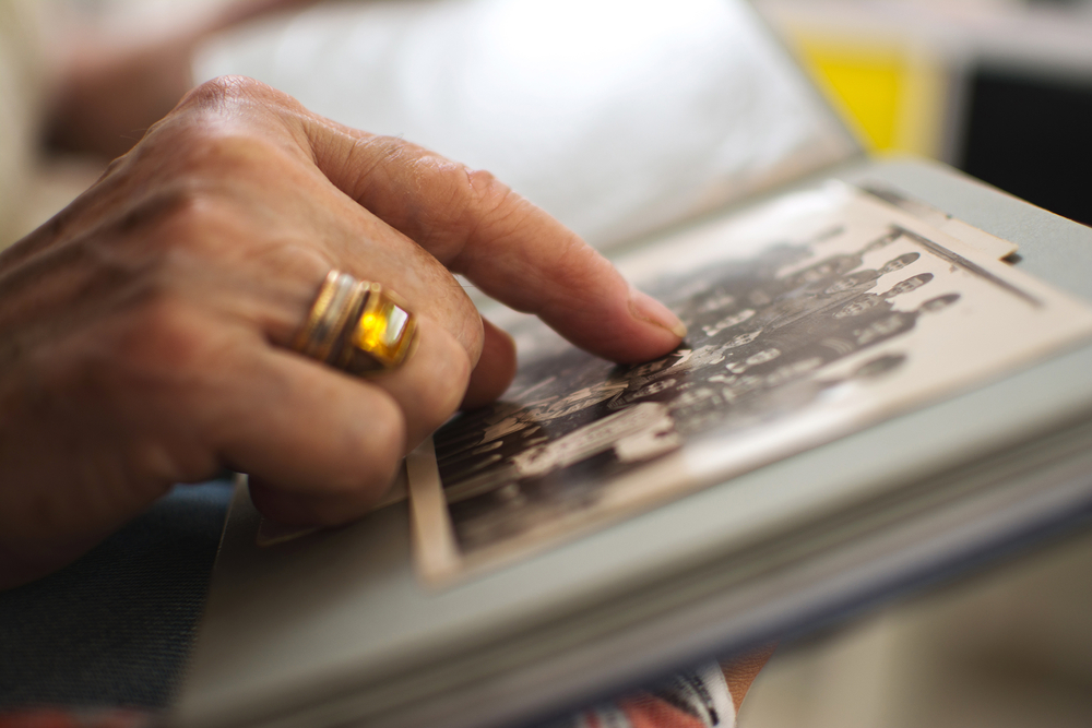 Senior woman's hand touching an old photo. Close up.