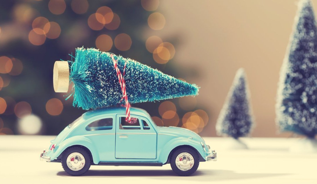 miniature VW bug with a christmas tree on top concept of traveling to celebrate the holidays