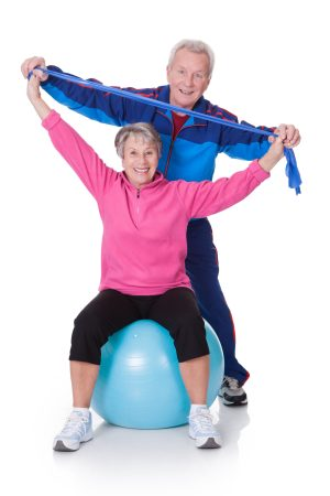 senior on a fitness ball with a personal trainer