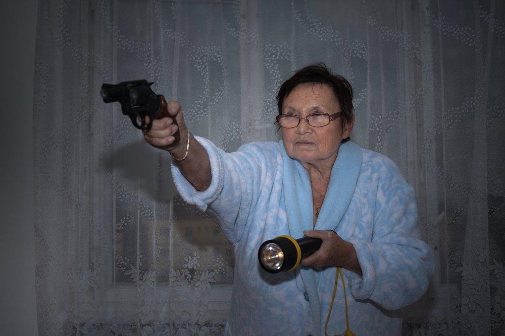 Scared senior woman aiming a gun and torch.