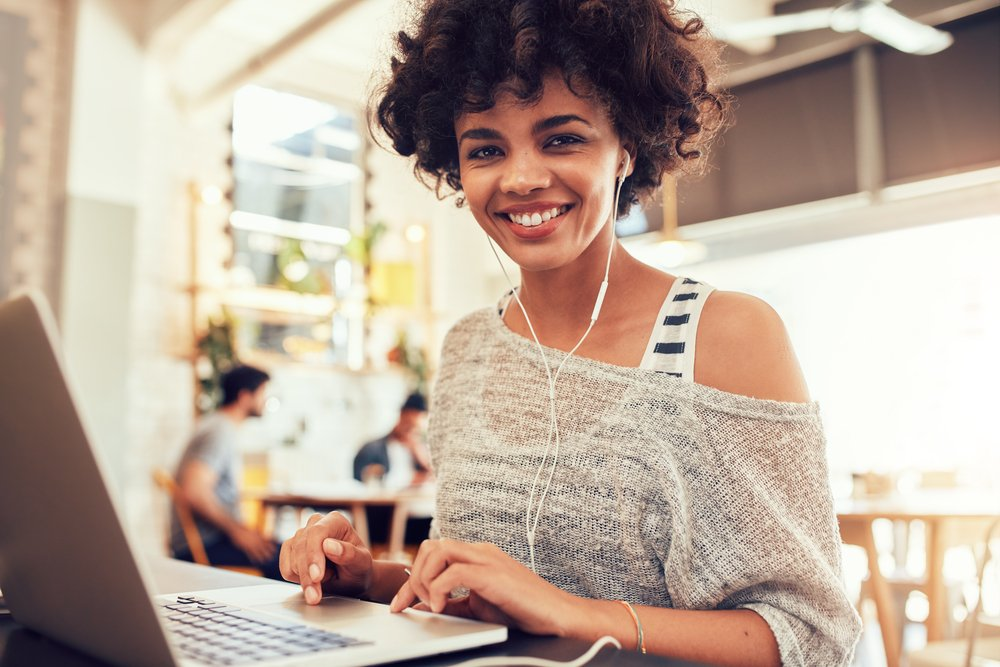 Portrait of happy young african woman with a laptop at cafe. Smiling woman sitting in coffee shop with a laptop