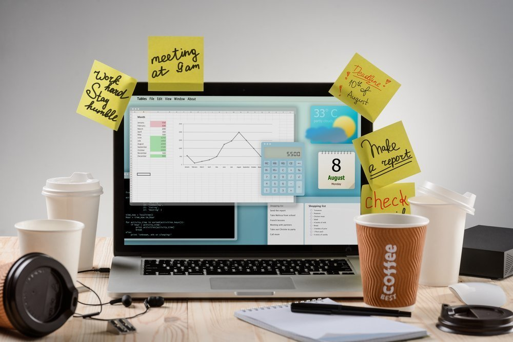 Hard working process with a lot of tasks written on yellow sticky notes on the monitor of the modern laptop. Little reminders for employee to stay organized. Worker with the lack of sleep.