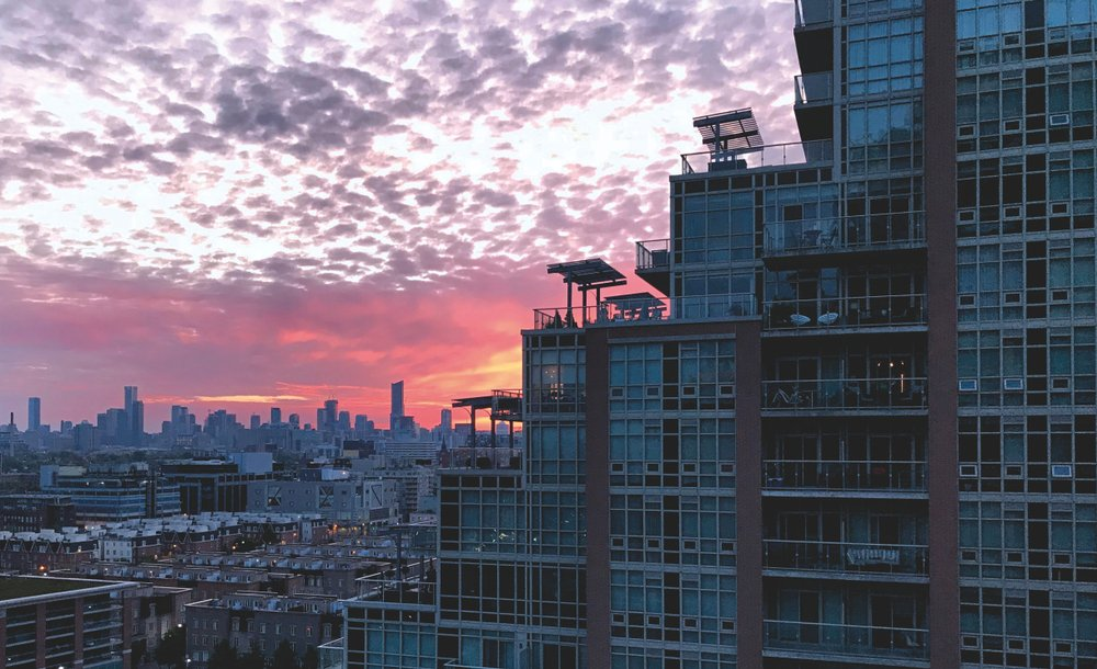 View of downtown Toronto, Ontario, Canada from Liberty Village. High view. Condos. Sunrise. Purple, pink and yellow sky.
