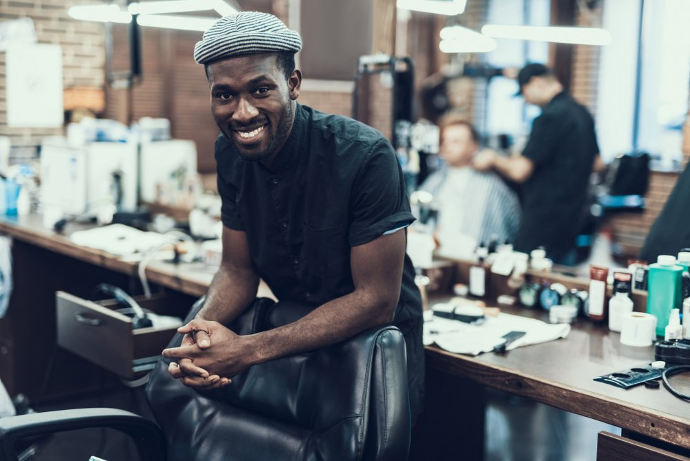 young black barber looks into the camera smiling and leaning against an empty chair. barber shop is in soft focus