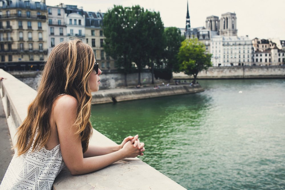White woman in her 30s on a bridge over the Seine river while walking on Champs-Elysees, Paris, France