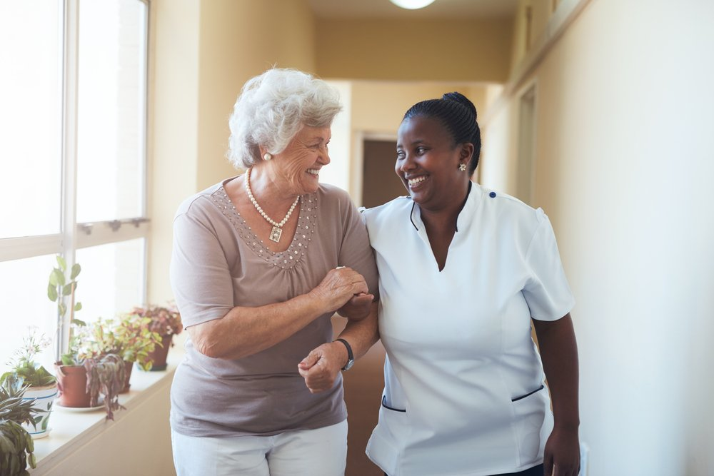 Portrait of smiling home caregiver and senior woman walking together through a corridor. Healthcare worker taking care of elderly woman