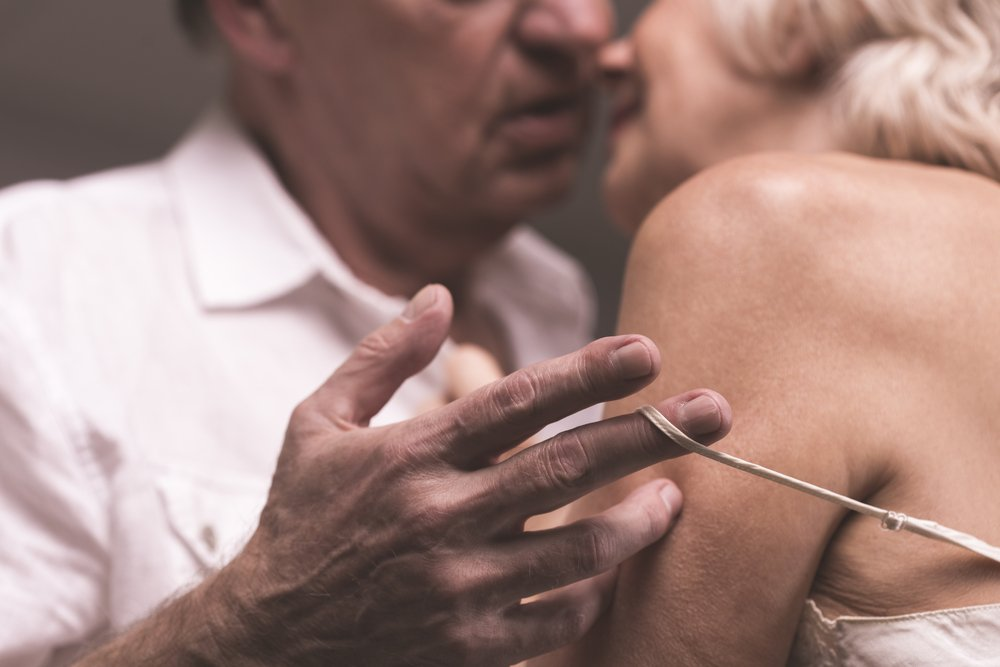 Elder couple bodies close to each other with the man's hand stripping shoulder-strap of woman's underwear