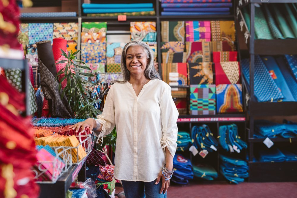 smiling black senior stands in a fabric store