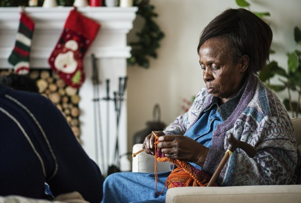 an elderly black woman knitting in front of a fireplace hung with christmas stockings because trying to find a stock photo of an elderly black woman is impossible