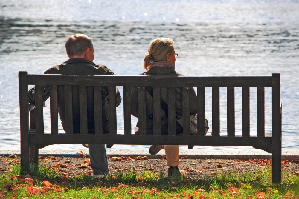 two people sitting on a bench near the water, talking. seen from behind