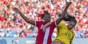 An ever-hopeful crowd shows the flag last weekend. Canada's national women's team met Brazil in a friendly match, which the visitors won 2-0 at BMO Field despite heroic efforts by Canada's Kadeisha Buchanan No. 3 and Sophie Schmitdt No. 13, here battling Brazil's high scoring star Marta No. 10, who netted both goals. The Canadians redeemed themselves Monday night in Ottawa, beating Brazil 1-0 in a rematch. Gerard Richardson photos.