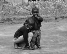 A big brother helping his little sister with her sandals in Layibi Village. I would often see small children like this wandering the streets in town as well.